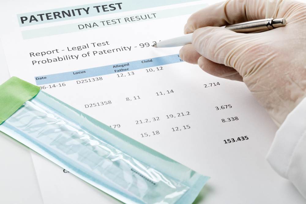 Gloved hand holding a pen above a paternity test.